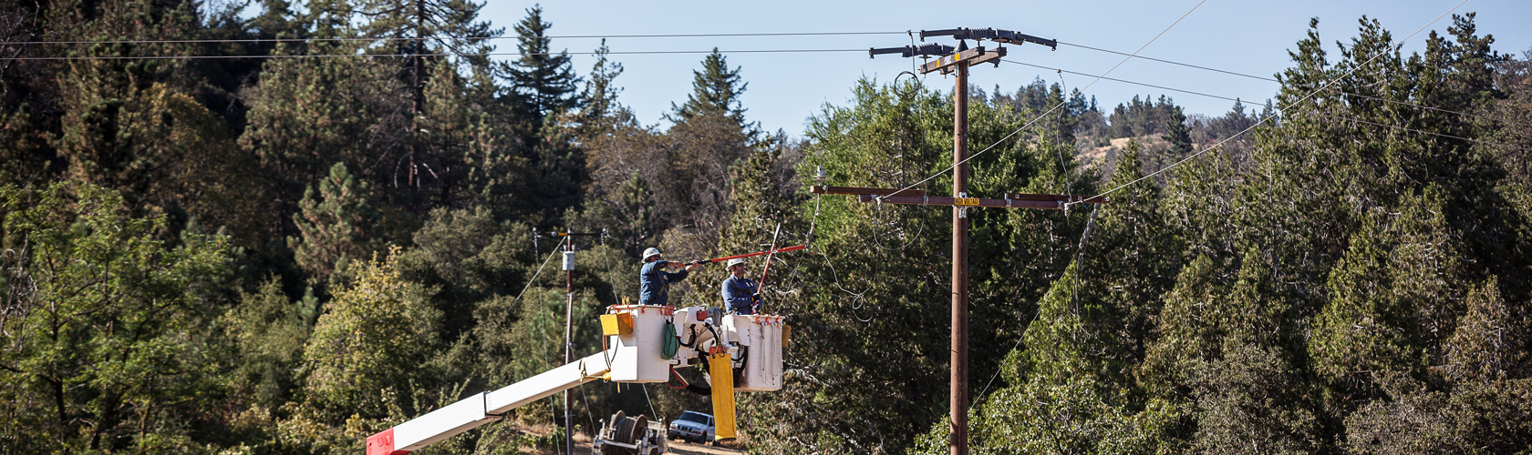 Utility employees working on steel power pole